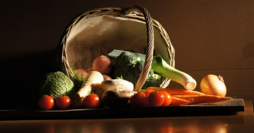 basked of vegetables photographed in low light.