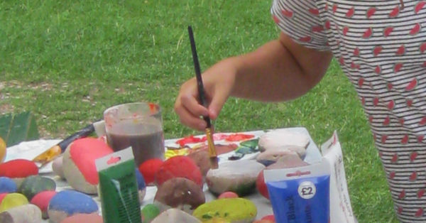 children with paints doing rock painting
